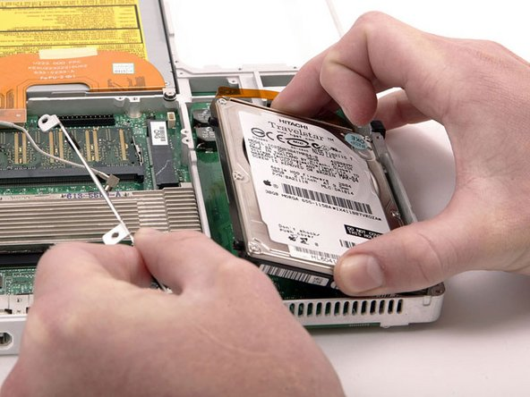 Lift the hard drive up and remove the metal bracket, then carefully lower the hard drive back into its compartment.