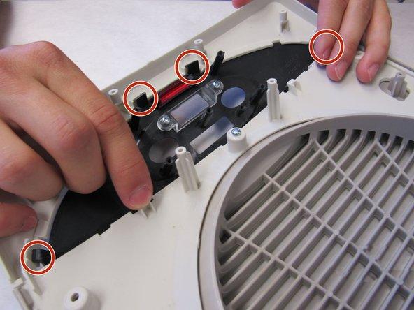 Using light finger pressure, carefully push the black plastic tabs off the white plastic hooks.