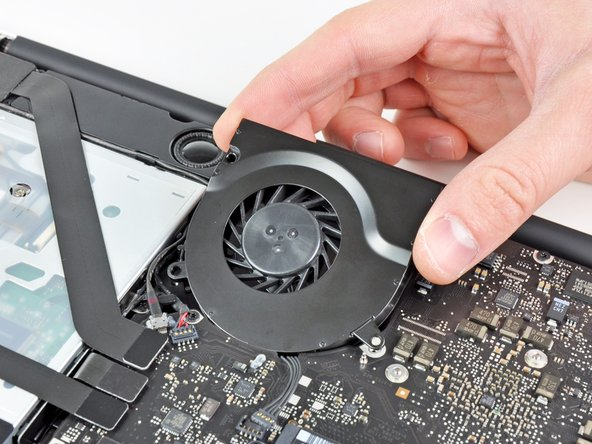 Lift the fan out of its recess in the logic board, minding its cable that may get caught.