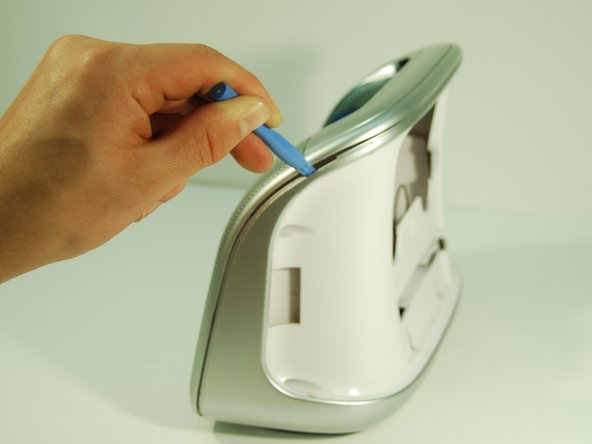 Pry open the inner back panel by inserting the plastic opening tool in the crack at the top corner.