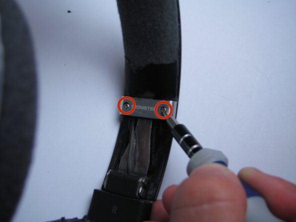 Using a T5 Torx screwdriver, remove the silver screws from the silver segment of the headband.
