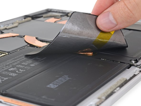 Searching for the gold at the end of the heatsink, we peel back some ... things. The Surface Pro 4 had a copper heat spreader, but these look like graphite.