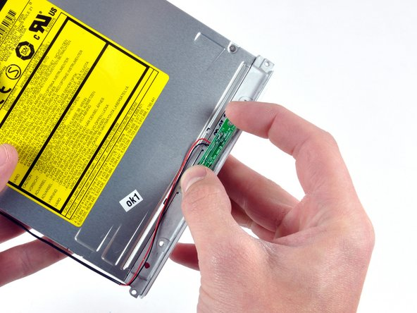 Peel the reed switch board from the optical drive and set it aside.