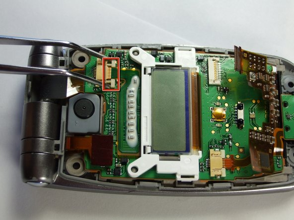 Unlock the minor LCD connector by applying bilateral pressure with tweezers, as shown.