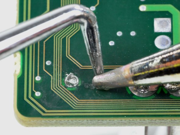 When the tool has completely passed through the hole, enlarge the hole by heating the top side of the solder pad while pressing through with the tool.