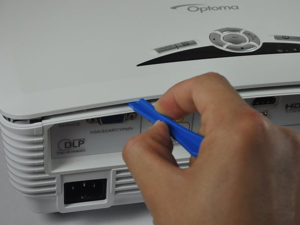 Use a plastic opening tool to gently pry the top cover off of the device.