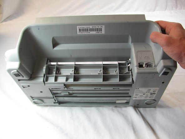 Rotate the printer 180 degrees and turn it up on to the front side, so that the back of the printer is facing up and the bottom facing you.