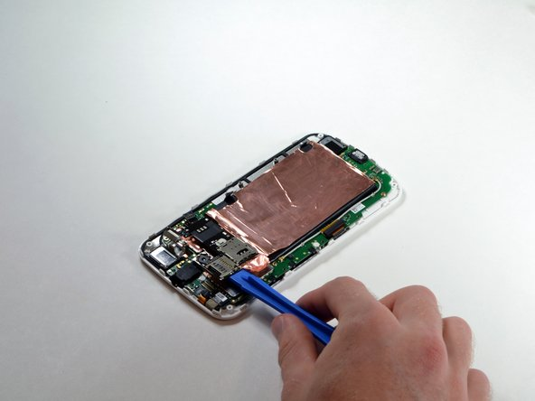 Using a plastic opening tool, carefully pry off the entire SIM/SD card reader component.