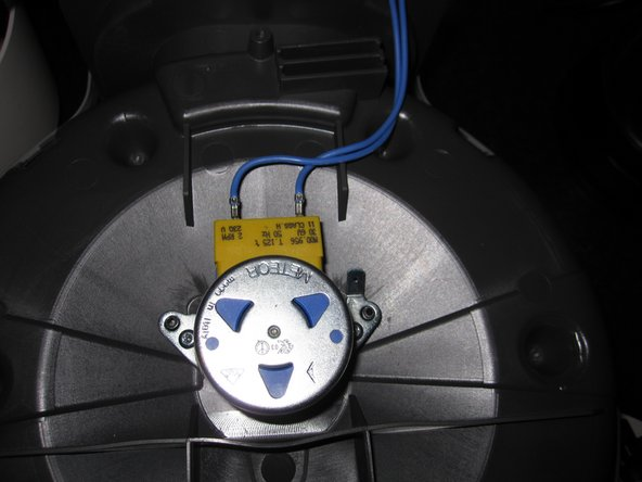 The motor is now exposed with the bottom cover removed. There are two security screws, the same size as the ones on the outside cover that need removed. There are two wires that need removed from the old motor and inserted into the new motor. The new can be secured in place and tightened with the screws.