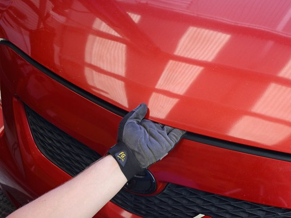 Raise the hood by simultaneously lifting and pressing up on the hood latch release (usually located beneath the front edge of the hood, near the center or center-right).