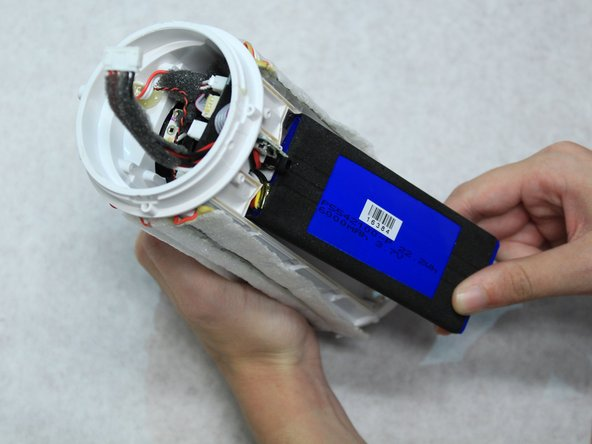 Use a hot air gun to soften the hot glue in order to fully remove the battery.