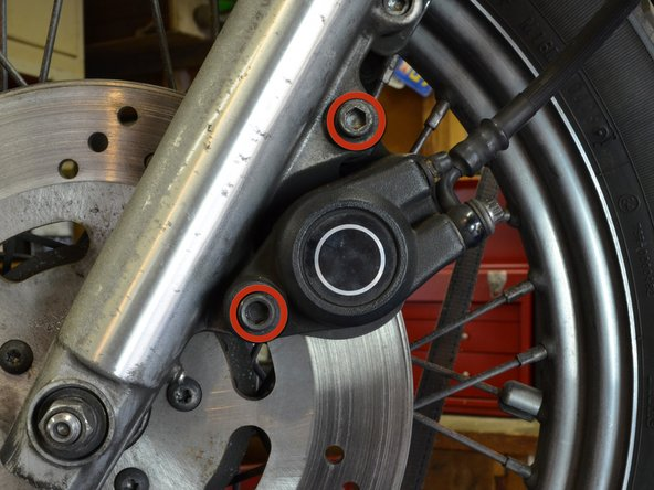 """Using a 1/4"""" hex head or allen wrench, unscrew the two bolts holding the front brake assembly to the fork."""