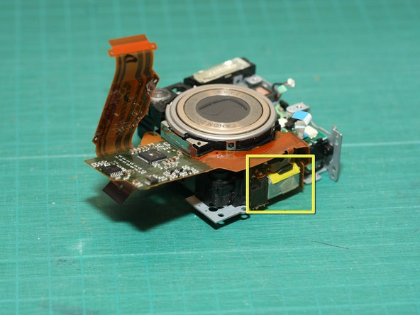 At the bottom of the lens module assembly is the larger of 2 motors (yellow square) - this is the motor that extends/retracts the lens.