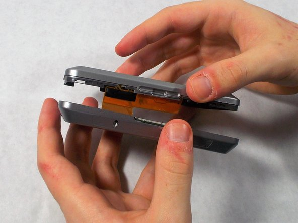 After the case front and rear are separated, carefully lay the two sides down without disconnecting or damaging the orange ribbon cable.