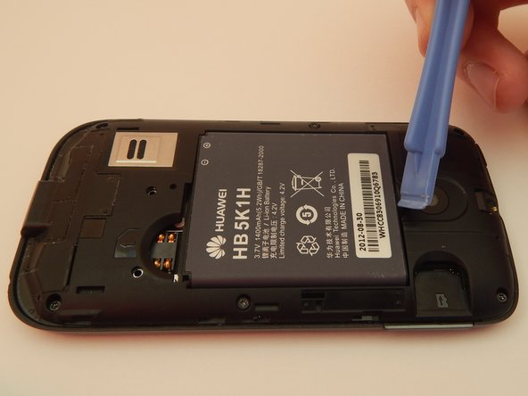 Place the plastic opening tool in the gap between the camera and battery.