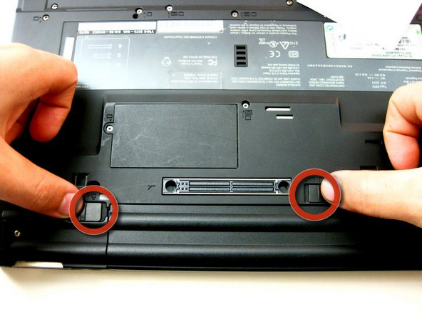 Flip the laptop over so the underside is facing you, then, release the 2 clips holding the battery on.