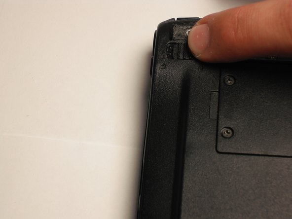 """Unlock the battery by sliding the switch located near the left hinge to the left """"unlocked"""" position."""