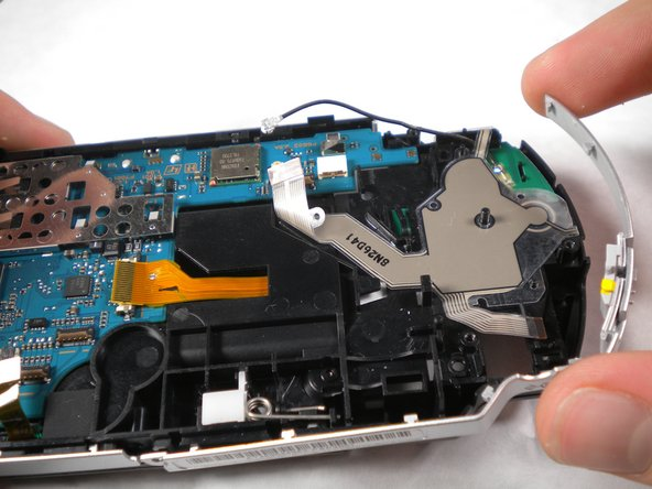 Lift the silver rim on the right side of the PSP up and off.