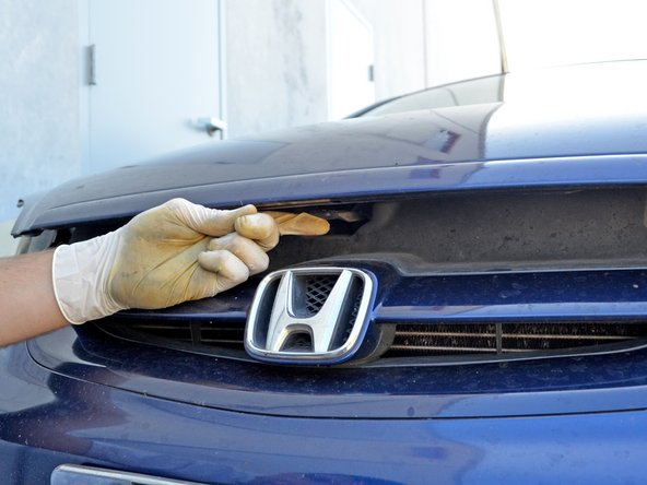 """The hood should be """"popped"""". Find the hood latch centered at the front of the hood, just above the Honda emblem."""