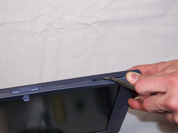 Using a spudger or another flat-headed tool, start to pry away the front bezel panel from the display assembly. While putting pressure on the front bezel, place the spudger on the seam connecting the front and rear bezel, and the clip attaching the two panels should start to come apart.
