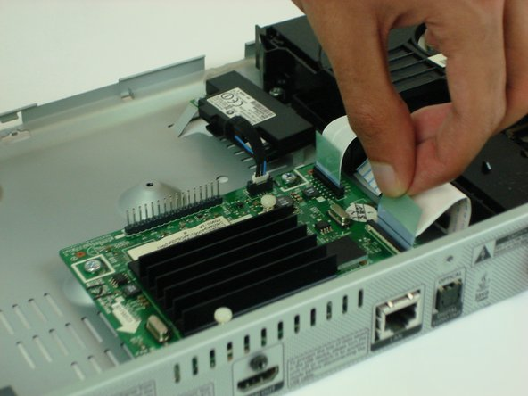 Remove the two ribbon cables from the Main Logic Board assembly by gently pulling up on the blue tab.