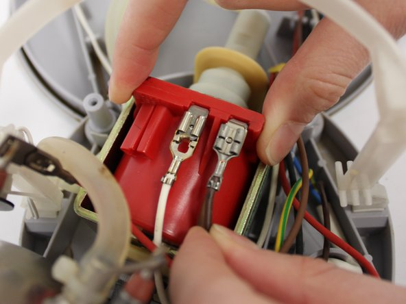 Disconnect the two cables (white-brown) from the red pump by pulling gently. If the cables are hard to remove, carefully use flat nose pliers to pull the cables.