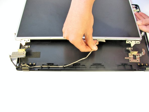 Gently unhook the wire from the back bezel to allow the LCD to be flipped over.