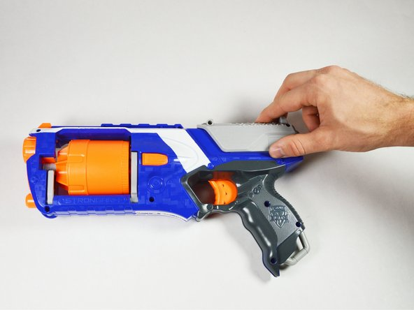 First, remove the outer parts of the blaster, starting with the top part of the cocking mechanism. Then remove the full cover itself.