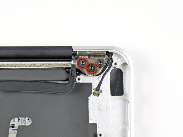 Remove the two 4.9 mm T8 Torx screw securing the antenna cable retainer on the left display hinge to the upper case.