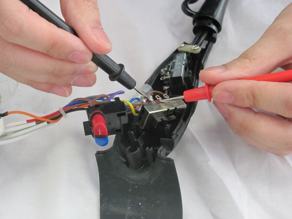 Bring the probes toward each switch to test for continuity.