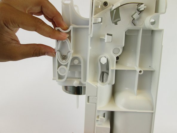 Remove the plastic oval and the spring within it.