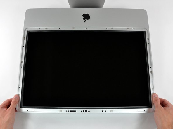 The front bezel is still attached to the iMac by the microphone cable.
