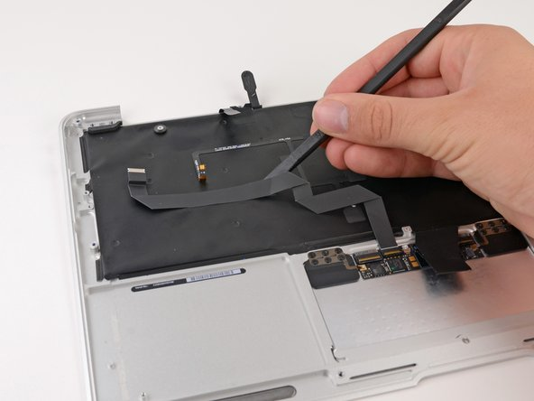 Use the flat end of a spudger to separate the trackpad ribbon cable from the underside of the keyboard.