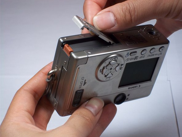 Hold the end of the battery cover that extends beyond the camera and lift it up.