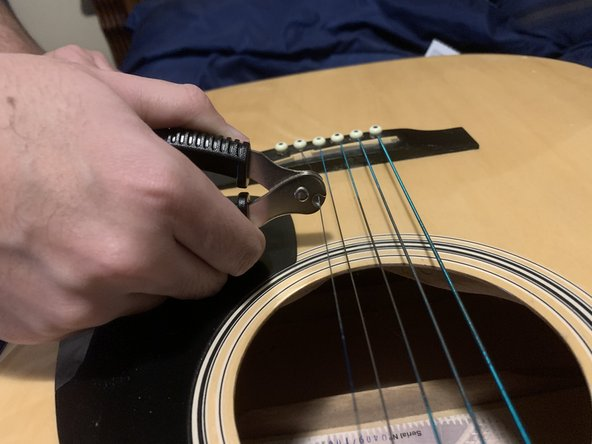 With the string clipper, clip the string under the neck of the guitar.