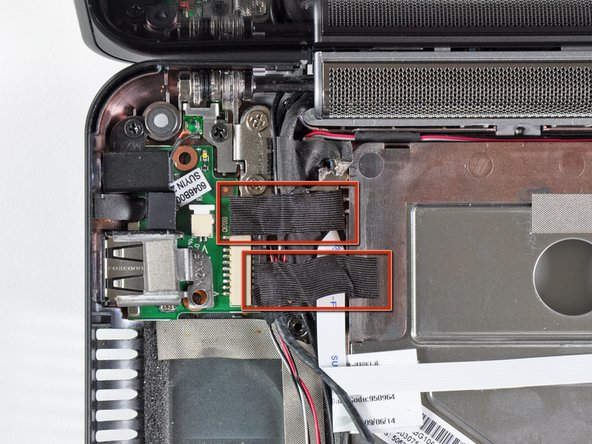 If present, remove the two pieces of tape covering the cables routed near the USB and power board.