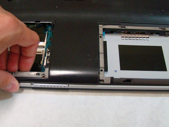 After removing the screws, use your fingers to lift the back cover off the laptop.