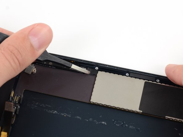 Use tweezers to peel up and remove the small piece of tape covering the button ribbon cable ZIF connector.