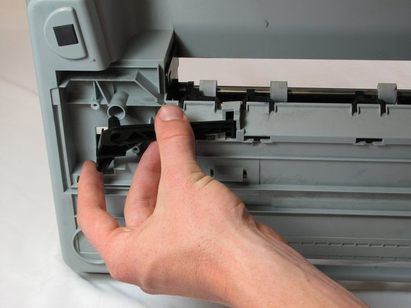 Remove the black plastic cross member from the bottom of the printer.