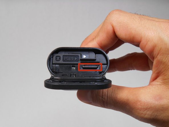 After sliding the rear panel to the side, open the door outward to reveal the memory card slot and battery tray.