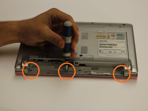 Using the bit driver and a Phillips #0 bit, remove the three circled screws, 5 mm in length.