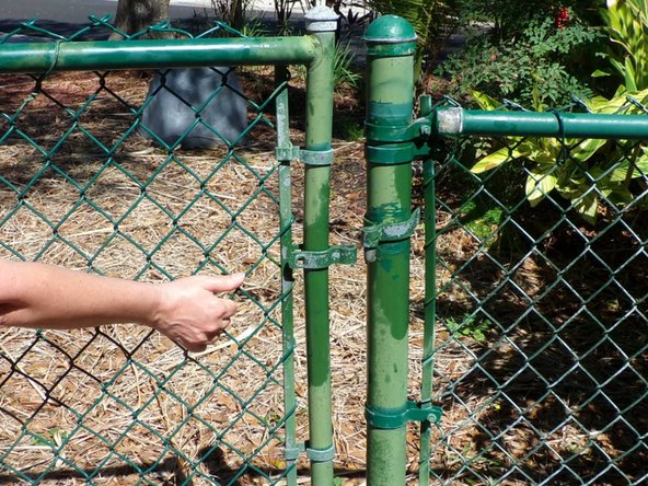 Slide the gate away from the fence post set it aside.