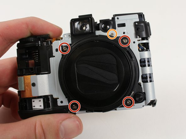 Reorient the camera so that black lens cover is facing you with viewfinder on top.