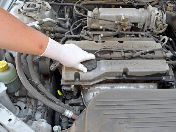 Locate the oil filler cap. It is on the front passenger side of the engine's valve cover.