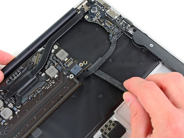Use the flat end of a spudger to free the adhesive loop securing the I/O board power cable to the upper case.