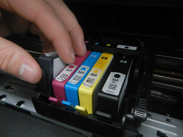 Remove each ink cartridge by pushing the tab and lifting the cartridge.