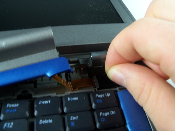 Locate the black tab at the upper right corner of the keyboard, and gently pull the black tab to the left to disconnect the hinge cover.