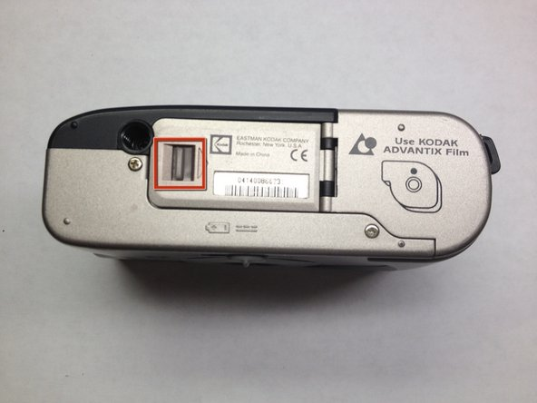 To open the cover of the battery slot, push the highlighted tab in the direction of the arrow next to it, and gently lift.