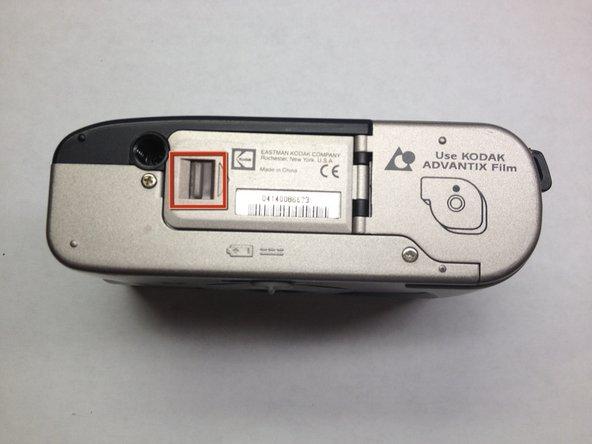 Pour ouvrir le couvercle du logement de la batterie, poussez la languette en surbrillance dans le sens de la flèche à côté et soulevez doucement.