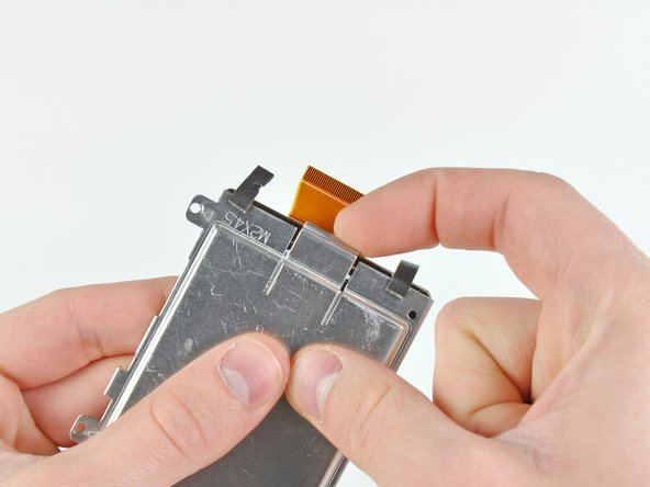 Lift up the center retaining tab on the hard drive enclosure and simultaneously push the hard drive out through the open end of the enclosure.